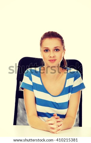 Smiling teenage woman sitting behind the desk - stock photo