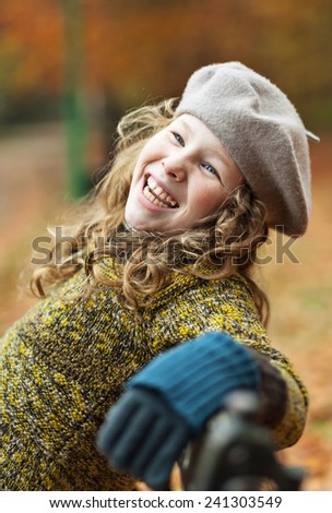Smiling teenager blond girl sitting on a bench in autumn park - stock photo