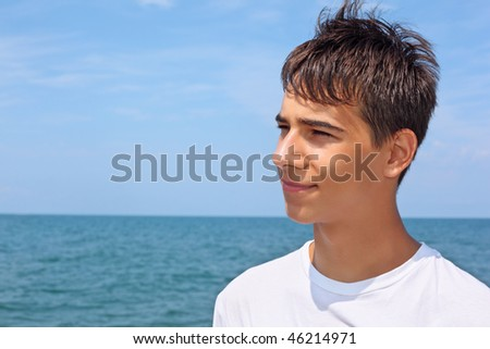 smiling teenager boy against sea, Looking afar - stock photo