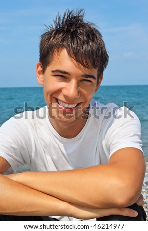smiling teenager boy against sea, Looking at camera - stock photo