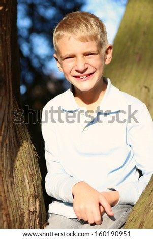 Smiling teenager boy sitting between the branches of the old big tree in the forest on a sunny autumn day - stock photo