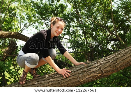 Smiling teenager climbing in a tree by a nice summer day