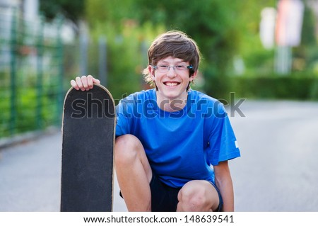 Smiling teenager crouching and holding his skateboard in a suburban setting.  - stock photo