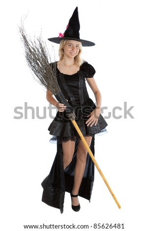 smiling teenager girl in Halloween witch with broom - stock photo