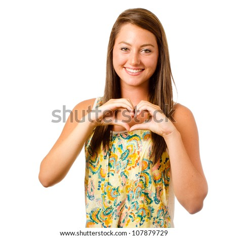 Smiling teenager girl making heart shape with her hands isolated on white - stock photo