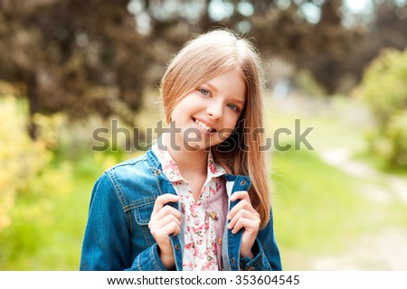 Smiling teenager girl 14-16 year old wearing denim jacket over nature background. Looking at camera. Teenagerhood.