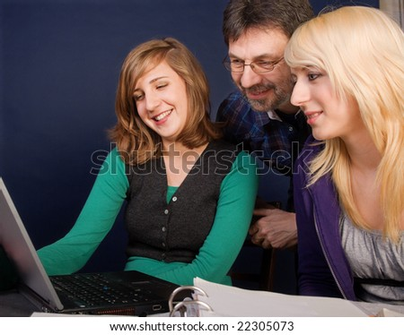 Smiling teenager girls and their father looking at laptop screen