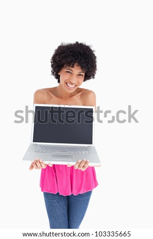 Smiling teenager holding her laptop with the screen in front of the camera - stock photo