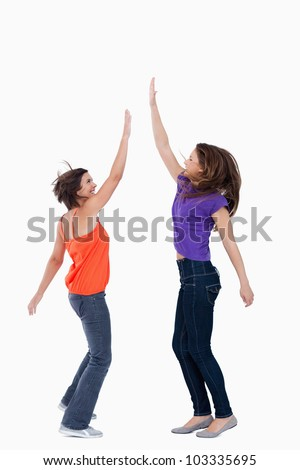 Smiling teenager keeping her hand in the air while her friend tries to touch it - stock photo