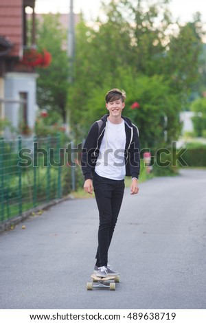 Smiling teenager on a longboard.
