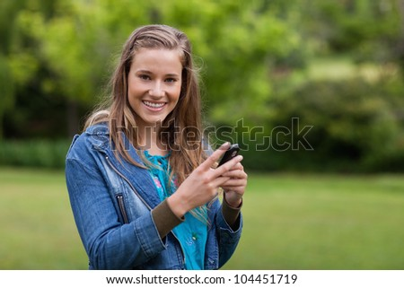 Smiling teenager sending a text with her cellphone
