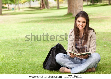 Smiling teenager sitting while holding a textbook in a park - stock photo
