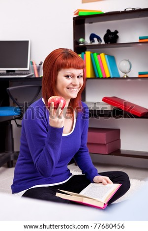 smiling teenager with apple and book at home