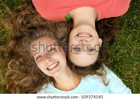 Smiling teenagers friends lying in a grass in a park