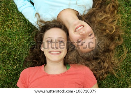 Smiling teenagers friends lying on a grass in a park - stock photo