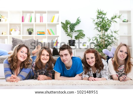 Smiling teenagers friends lying on floor in row - stock photo