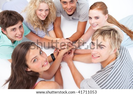 Smiling Teenagers lying on the floor in a circle playing hands games - stock photo