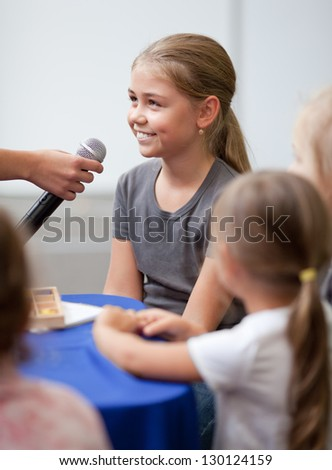 Smiling ten year old girl speaks into handheld microphone. A woman's hand holds a microphone in front of her - stock photo