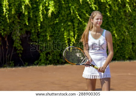 Smiling tennis athlete on play-field. Junior female stays on clay tennis court white dress with miniskirt holds racket smiling positive green fence blurred background - stock photo