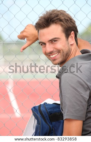 Smiling tennis player standing outside a hard court - stock photo