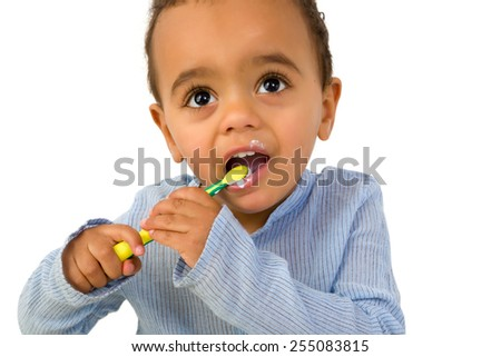Smiling 18th month old African toddler boy brushing his teeth - stock photo