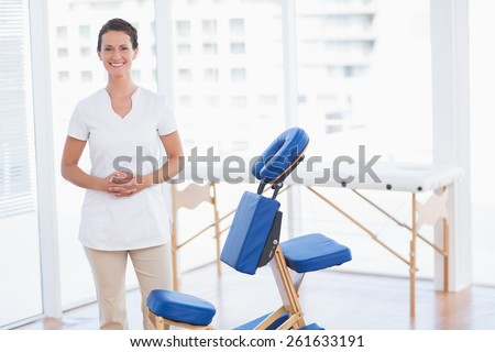 Smiling therapist smiling at camera in medical office - stock photo