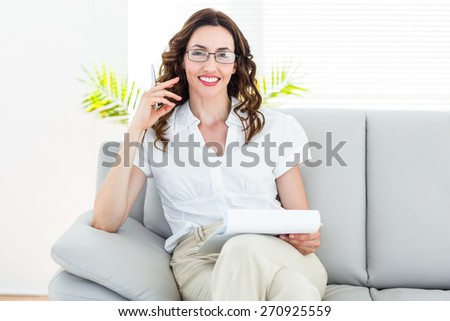 Smiling therapist taking notes on white background - stock photo