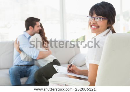 Smiling therapist with patients hugging behind her in the office