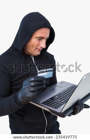 Smiling thief in hood jacket using laptop and credit card on white background - stock photo