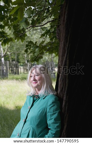 Smiling thoughtful middle aged woman standing beneath a tree - stock photo