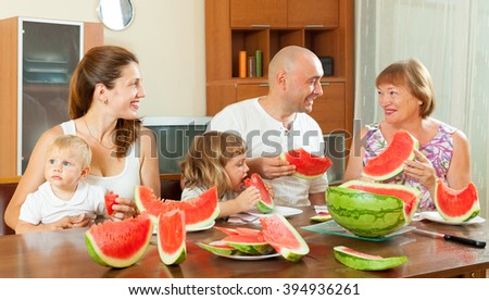 Smiling three generations family eating watermelon at home interior