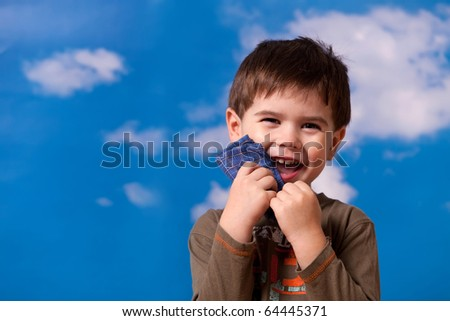 Smiling three year old boy portrait on blue sky background