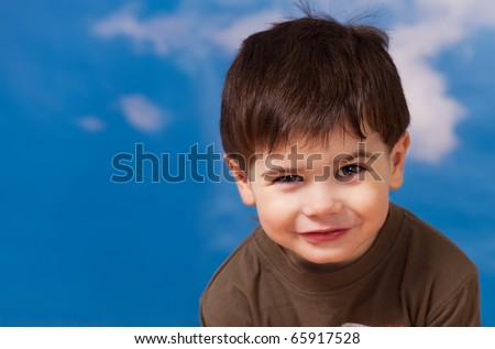 Smiling three year old boy portrait on blue sky background - stock photo