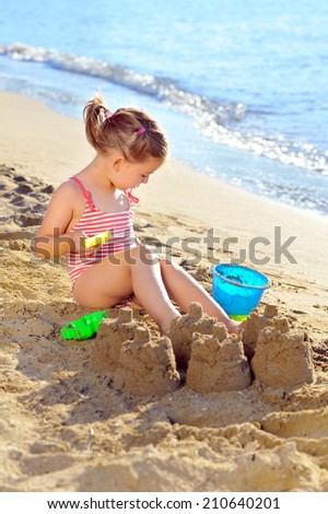 Smiling toddler girl playing with her toys at beach