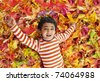 Smiling Toddler Lying on a Bed of Colorful Autumn Leaves - stock photo