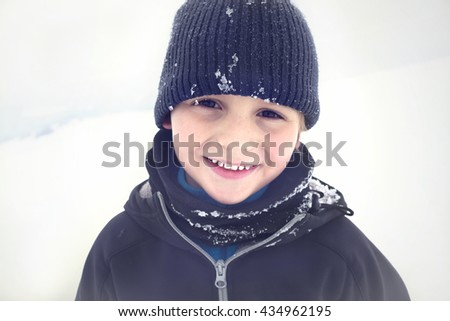 Smiling toddler posing for pictures in the snow - stock photo
