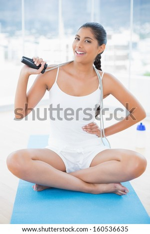 Smiling toned brunette sitting on floor with skipping rope in bright room