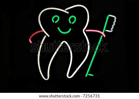 Smiling tooth holding a toothbrush neon sign - stock photo