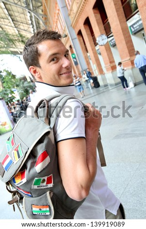 Smiling tourist with backback in train station - stock photo