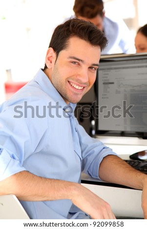 Smiling trader in front of desktop computer - stock photo
