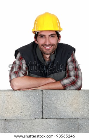 Smiling tradesman leaning on a stone wall - stock photo