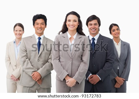 Smiling tradeswoman standing with her colleagues against a white background