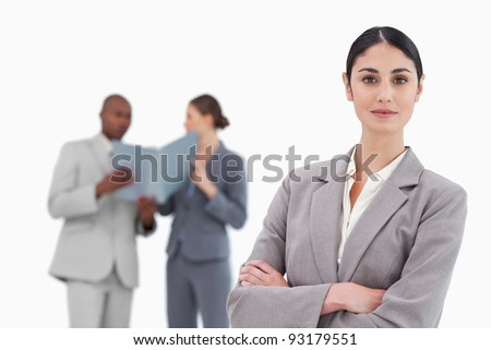 Smiling tradeswoman with arms crossed and team behind her against a white background