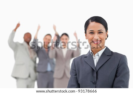 Smiling tradeswoman with cheering team behind her against a white background - stock photo