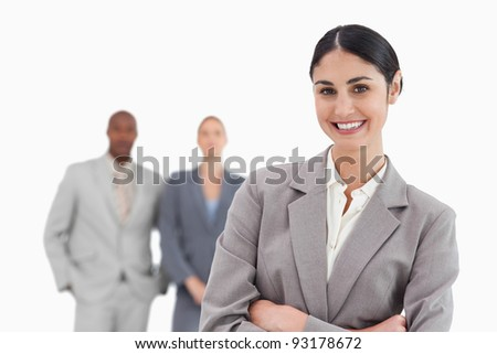 Smiling tradeswoman with co-workers behind her against a white background