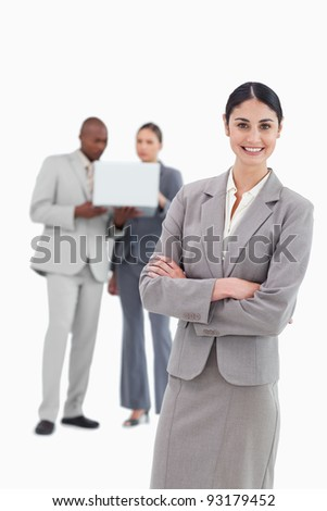 Smiling tradeswoman with folded arms and co-workers behind her against a white background