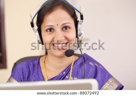 Smiling traditional Indian Woman wearing headset - stock photo