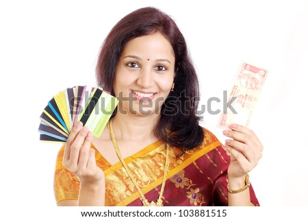 Smiling traditional Indian woman with Indian currency and credit cards - stock photo