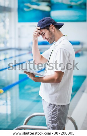Smiling trainer holding clipboard at the pool - stock photo