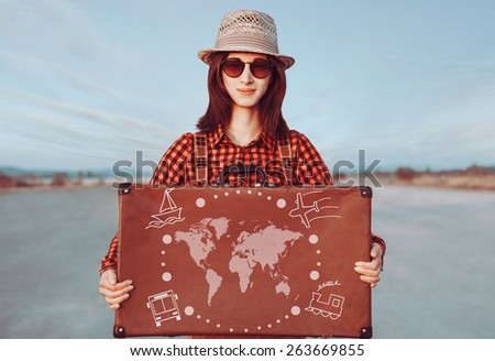 Smiling traveler woman holding suitcase. Map of the world and types of transport on a suitcase. Concept of travel - stock photo